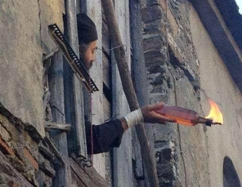 Monje del monasterio de Esfigmenu lanza un cóctel Molotov